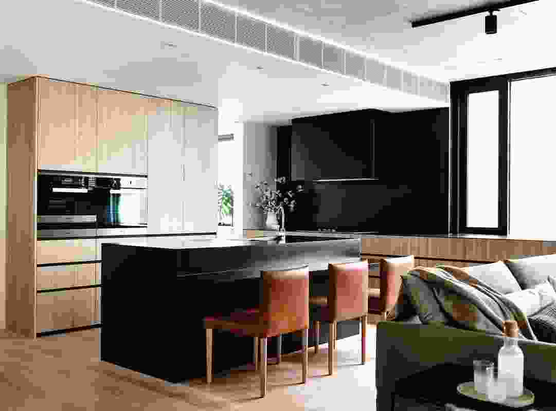 The kitchen combines the warmth of timber joinery with an onyx-hued island bench, splashback and oversized rangehood.